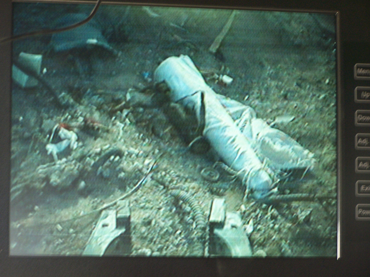 The robot finds an IED -- a wired-up artillery shell, wrapped in white plastic.