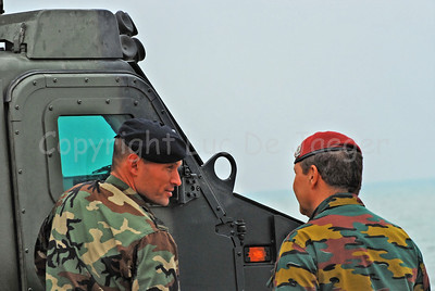A Dutch Marine (left) talks with a Belgian paratrooper (right) in front of the Bandvagn BvS10 Viking which is in use by the Dutch Royal Marines. They assist during Operation Storm Tide in Ostend (Oostende), Belgium, a Field Training Exercise (FTX) with Belgian Paratroopers.