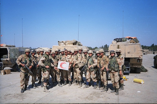 "Most of the 1-505 medics at Talil Airbase, Iraq, posing with Bn CSM Kendall with a ""Red Crescent"" flag he had liberated and presented to the medics.  I later had the flag and this photo framed and presented to the battalion.  Supposedly it hangs in the ""H-Minus Room"" in the battalion area at Fort Bragg.<br /> <br /> Pictured from left to right are - Tiscani, Gallagher, Cabrera, Breeding, Kendall, Warden, Loughman, ?attached 307th Med Bn medic, Stanlione, Brasfield, Vansandt, Stressman, Bates, Whitlock, Jacobson, Lando, Sullivan, Moodie or Chipman, Swann, Isenhower, Ward."