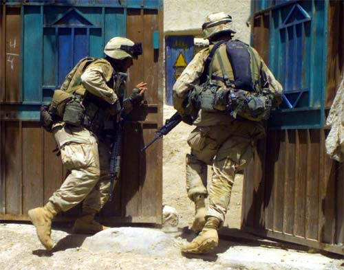Marines push open the heavy doors of a compund in south-central Afghanistan.