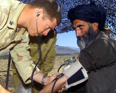 A Marine examines an Afghan village elder during a medical civil affairs project near Tarin Kowt, Afghanistan.