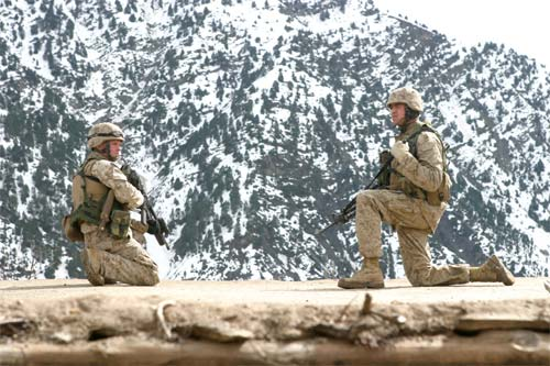 Two Marines provide security on a rooftop while other Marines conduct searches through buildings during Operation Mavericks, an operation that Marines conducted to capture suspected terrorists in the vicinity of Methar Lam, Afghanistan.