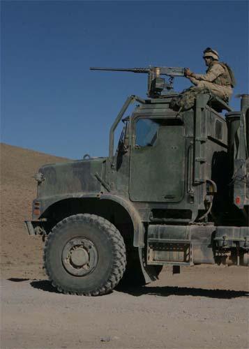 A Marine stands guard behind his .50-caliber machine gun mounted on a seven-ton truck.