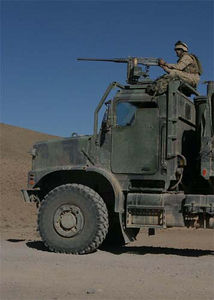 A Marine stands guard behind his .50-caliber machine gun mounted on a seven-ton truck.