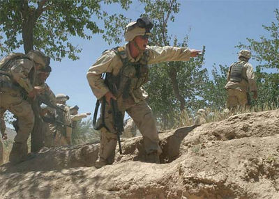 A sergeant yells for his Marines to take cover as sniper fire impacts around them during a fight with anti-coalition militia in central Afghanistan.