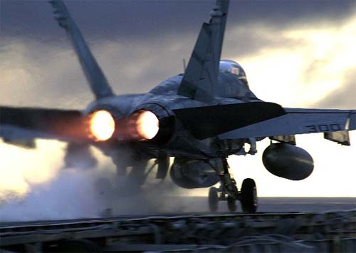 An F/A-18C Hornet launches from the flight deck of the conventionally powered aircraft carrier USS Constellation (CV 64) for a sunset training flight.
