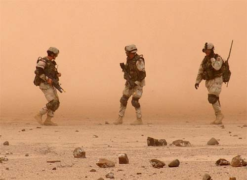 Infantrymen make their way through a dust storm created by a CH-53E helicopter during a combat recovery exercise in rural Djibouti.