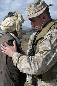 A Naval Medical Officer checks a local man's heartbeat during a Medcap operation.