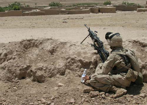 A Marine provides overwatch of a village in Afghanistan's Oruzgan province as his fellow Marines move in to search the buildings for weapons and enemy fighters.