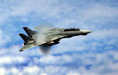 "An F-14D Tomcat assigned to the ""Tomcatters"" of Fighter Squadron Three One (VF-31) performs a high-speed fly-by past USS Theodore Roosevelt (CVN 71)."