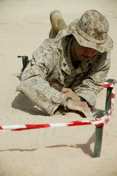 Carefully sifting through the desert sand, a Marine searches for mines during Explosive Hazards Awareness Training held aboard Al Asad, Iraq