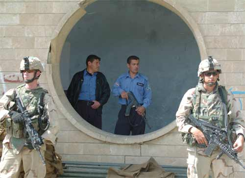 Soldiers assist Iraqi policemen in guarding their police station from terrorist attack in Mosul, Iraq.