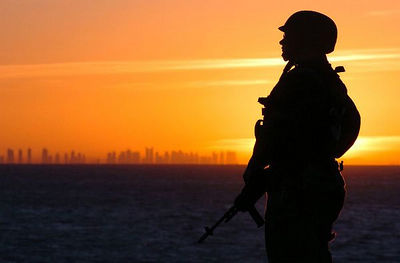 Standing watch on the flight deck during a sunset aboard the amphibious assault ship USS Tarawa (LHA 1).