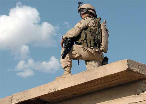 An infantryman provides surveillance from a rooftop while his fellow Soldiers search for weapons caches during a mission in Kirkuk, Iraq.
