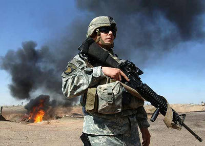 A soldier stands before a car fire in Iraq.