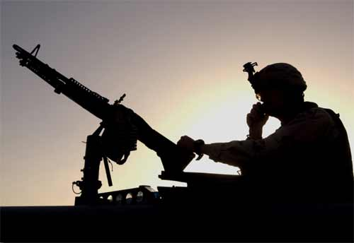 Silhouetted against the sun, a Soldier communicates via radio while performing security for a patrol through the village of Al Asyria, Iraq.