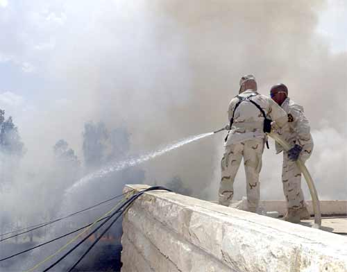 Soldiers fight a fire caused by a mortar attack on Camp Freedom in Mosul, Iraq.