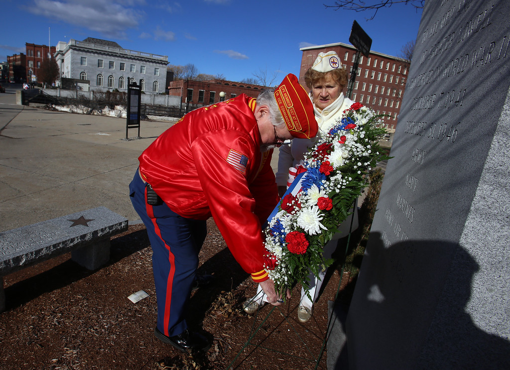 . Greater Lowell Veterans Council\'s Pearl Harbor Day observance at Lowell Memorial Auditorium. Sergeant at Arms Ron Roy of Lowell and Irene Finneral of Lowell, who is a Gold Star wife and Gold Star mother, lay a wreath at the WWII memorial. (SUN/Julia Malakie)