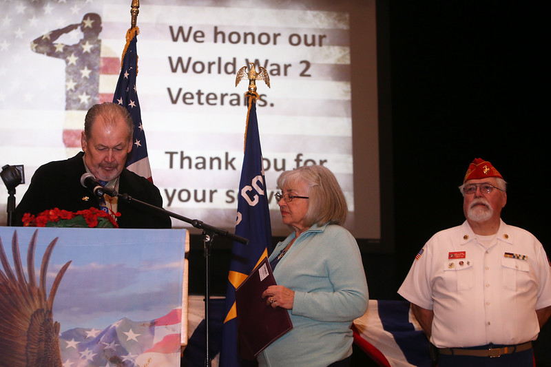 Greater Lowell Veterans Council's Pearl Harbor Day observance at Lowell Memorial Auditorium. Kenneth Powers of Lowell introduces his wife Rita Powers, who was born in Poland and spoke about her father, who escaped the Holocaust, and thanked the military for saving her father's life. At right is Sergeant at Arms Ron Roy of Lowell. (SUN/Julia Malakie)
