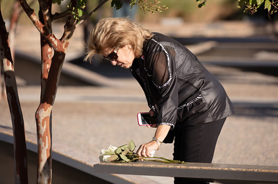 Betsy Wolk of Columbia, Md. lays a rose visit the bench dedicated to their late son-in-law, Navy Lt. Darin Pontell.