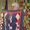 Ernie Blasetti of Ayer is presented with a handmade quilt from Central MA Quilts of Valor, the local branch of the organization that gives the quilts to veterans to hone their sacrifice. Quilts of Valor volunteer Joan Schwerin of Ayer holds up the quilt for Blasetti. Hanging on the wall is the first Quilt of Valor Schwerin made herself, for her husband who served in Vietnam. (SUN/Julia Malakie)