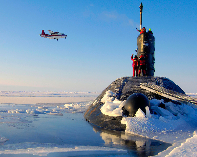 HMS Tireless is shown after surfacing in the North Pole ice cap region.  The crew are waving to a supply plane as it prepares to land at the US Navy's Applied Physics Laboratory Ice Station (APLIS).<br /> <br /> HMS Tireless, is a Trafalgar Class Nuclear-Powered Attack Submarine (SSN) Fleet Submarine.