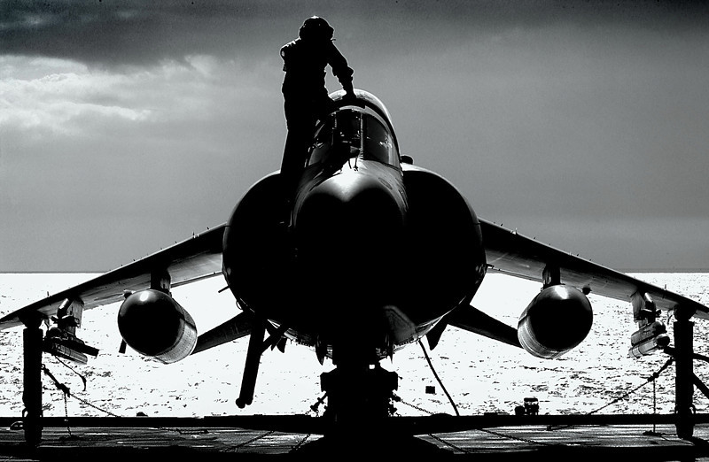 A pilot climbing into the cockpit of a Sea Harrier FA2, on the upper deck of HMS Illustrious, an Aircraft Carrier, as she sailed through the Straits of Gibraltar.<br /> <br /> This image was submitted as part of the Peregrine 06 Photographic Competition.