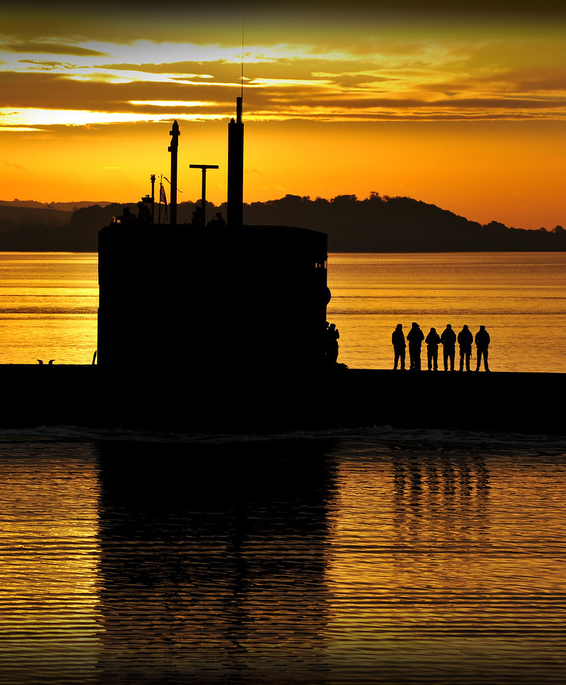 Trafalgar Class submarine SSN (Ship Submersible Nuclear) HMS Triumph, glides into HM Naval Base Clyde in the early morning sun following a patrol.<br /> <br /> The Triumph of today is somewhat different from her predecessors.  Built by VSEL at Barrow-in-Furness, she was commissioned in October 1991 and is the seventh and last of the Trafalgar class.  Since commissioning, the submarine has completed a number of notable patrols from the North Atlantic to the Far East.<br /> <br /> Between 2005 and 2009, Triumph went through a long overhaul period to refuel the reactor, complete essential maintenance and repairs. During this long overhaul period, the vessel's equipment and sensors were upgraded to make her one of the most potent and advanced submarines in the flotilla.