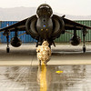 A Harrier from 800 Naval Air Squadron under its hangar in Afghanistan with engines running whilst a ground crew member runs checks on the aircraft's underside in the rain.