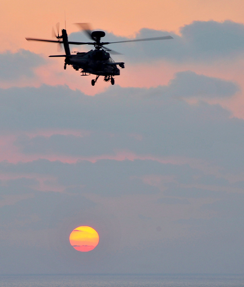 An Army Apache attack helicopter flys towards the setting sun from HMS Ocean in the Mediterranean Sea.<br /> <br /> On 18th September Apaches embarked on HMS Ocean for Operation Ellamy took part in landing practice in preparation for an operational period.