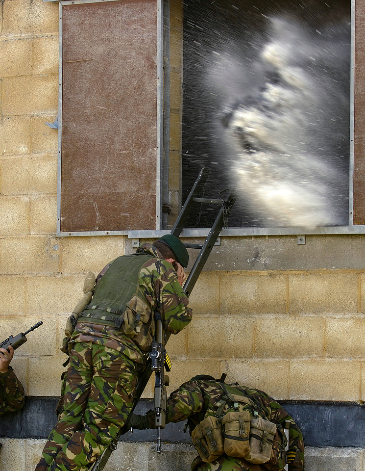 A Royal Marine covers his ears and shelters after throwing a hand grenade into a building during training on FIBUA (Fighting In a Built Up Area). The Marines were from Charlie company, 40 Commando and excercising at Copehill Down, Salisbury Plain, Wiltshire.