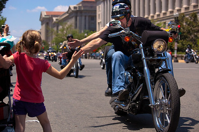 Rolling Thunder biker slaps the hand of young Aubrey Congdon on Constitution Ave, in Washington DC. Aubrey's dad is recovering from wounds at Walter Reed. On the morning of May 30, 2010 on Memorial Day Weekend Thousands of Rolling Thunder motorcycles ride through Washington DC in an annual demonstration seeking to improve veteran benefits and resolve POW/MIA issues.  Rolling Thunder has evolved to be not only a demonstration for the POW/MIA issue but also a demonstration of patriotism and respect for soldiers and veterans from all wars. (Photo by Jeff Malet)