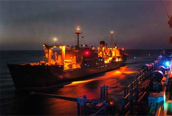 Night view of an underway replenishment oiler.