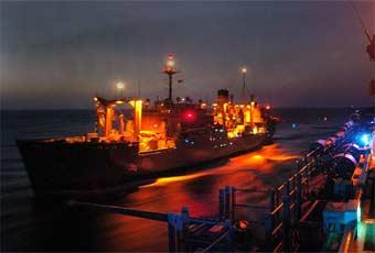 Night view of an underway replenishment oiler.