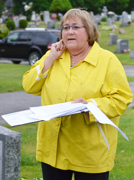 Rachel Howe, of Leominster, who has been volunteering for 25 years, helped by placing flags on the graves of veterans at St. Leo's Cemetery in Leominster on Saturday morning. SENTINEL & ENTERPRISE / Ashley Green