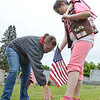 Kristen Dube, of Leominster, helps her daughter Megan Dube, 9, a Girl Scout, place flags on the graves of veterans at St. Leo's Cemetery in Leominster on Saturday morning. SENTINEL & ENTERPRISE / Ashley Green