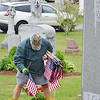 Mike Lannacone, of Leominster, places flags on the graves of veterans at St. Leo's Cemetery in Leominster on Saturday morning. SENTINEL & ENTERPRISE / Ashley Green