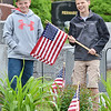 Andrew Fital, 12, and Lance Dobransky, 13, place flags on the graves of veterans at St. Leo's Cemetery as part of their service project for the National Junior Honor Society.  SENTINEL & ENTERPRISE / Ashley Green