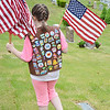 Girl Scout Megan Dube, 9, of Leominster, places flags on the graves of veterans at St. Leo's Cemetery in Leominster on Saturday morning. SENTINEL & ENTERPRISE / Ashley Green
