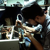 Electronics Technician 2nd Class (ET2) Robert Stone replaces a component in a microwave radio power supply.
