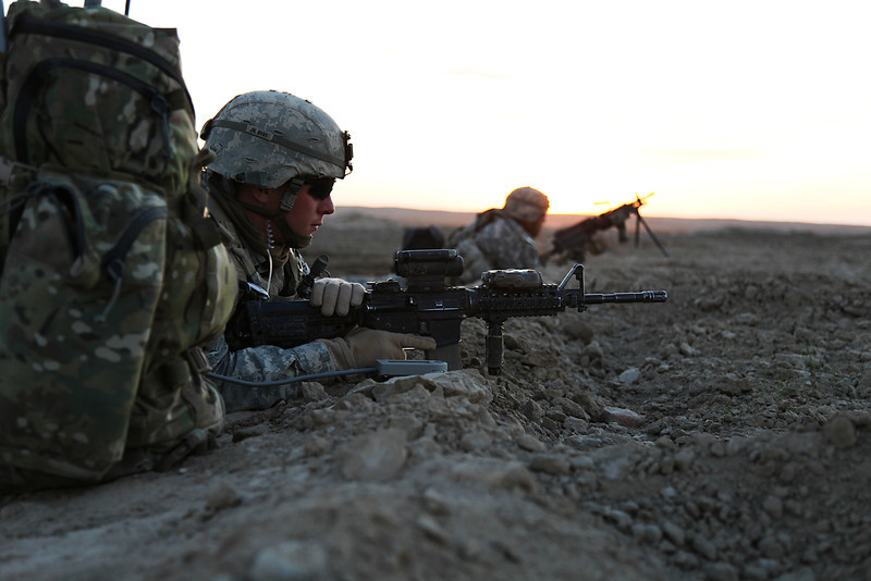 U.S. Soldiers with 4th Platoon, Golf Company, 3rd Squadron, 2nd Stryker Cavalry Regiment (SCR) stand guard as the company's 1st Platoon stages in preparation for extraction after conducting clearing operations in Chesmah, Kandahar province, Afghanistan, Jan. 18, 2011. Soldiers with 3/2 SCR worked with the Afghan National Army 205th Corps to clear Chesmah and build relations with Afghans. (U.S. Army photo by Cpl. Carol A. Lehman/Released)