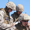 U.S. Marine Corps Major Thomas Campbell III, an Air Officer Department Instructor for Marine Aviation and Weapons Tactics Squadron One (MAWTS-1) plots coordinates on a map while a U.S. Marine from 1st Battalion, 1st Marine Regiment relays instructions with a radio on Observation Point Feets, Calif. during Assault Support Training 1 (AST-1), May 3, 2010. AST-1 is a training operation integrating different aircraft and ground forces to assault, capture, and evacuate an airfield during Weapons and Tactics Instructor Course 2-10, hosted by MAWTS-1. (U.S. Marine Corps Photo by Sgt Benjamin R. Reynolds)