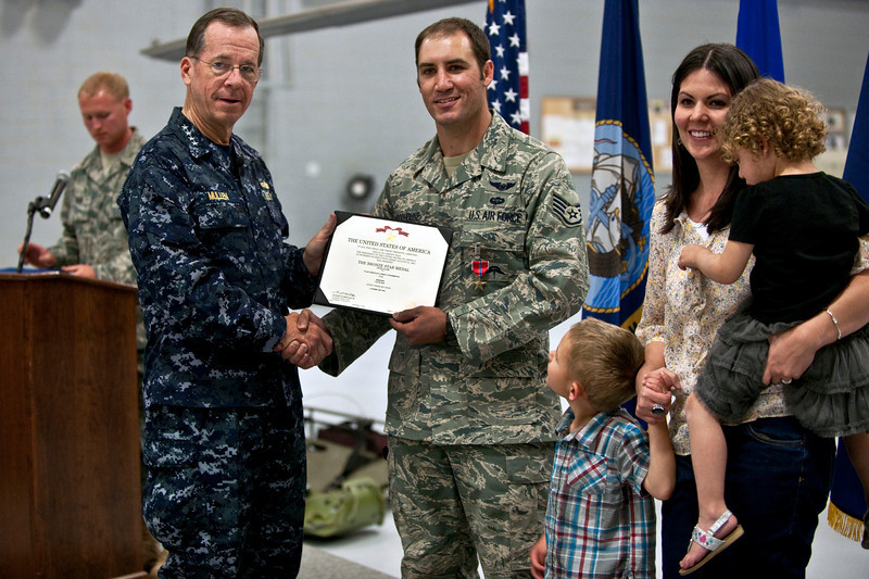 Chairman of the Joint Chiefs of Staff Navy Adm. Mike Mullen, center left, poses for a photo after awarding the Bronze Star with a combat valor device to Air Force Staff Sgt. Asher Woodhouse, center right, a pararescueman with the 58th Rescue Squadron, at Nellis Air Force Base, Nev., April 13, 2011. Woodhouse was one of three pararescuemen awarded the Bronze Star for heroic actions while rescuing U.S. Soldiers in Afghanistan in 2010.  (U.S. Air Force photo by Tech. Sgt. Michael R. Holzworth/Released)