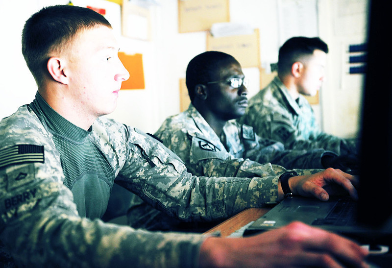 U.S. Army Pfc. Anthony Berry, left, Sgt. Antwone Coverdale and Pfc. Brandon Parsons, all from the Security Forces Advisory Team 4, 1st Brigade Combat Team (Heavy), 4th Infantry Division, check their computers shortly after a phone call came into the Operations Coordination Center (OCCP) for the province of Kandahar, Afghanistan, Dec. 8, 2010. The OCCP was an information hub and included Afghan National Security Forces liaisons and their coalition counterparts. Reports fed into the center, and the staff assessed and selected the appropriate agency to respond to the situation. (U.S. Air Force photo by Senior Airman Daryl Knee/Released)