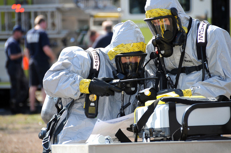 U.S. Air Force Senior Airman Harold Tamondong, left, and Airman 1st Class Greg Rollings work together at the crash site to identify potential hazards while clad in their hazardous material suits during a major accident response exercise at Keesler Air Force Base in Biloxi, Miss., Feb. 17, 2011. The Airmen are assigned to the 81st Aerospace Medicine Squadron. (U.S. Air Force photo by Kemberly Groue/Released)