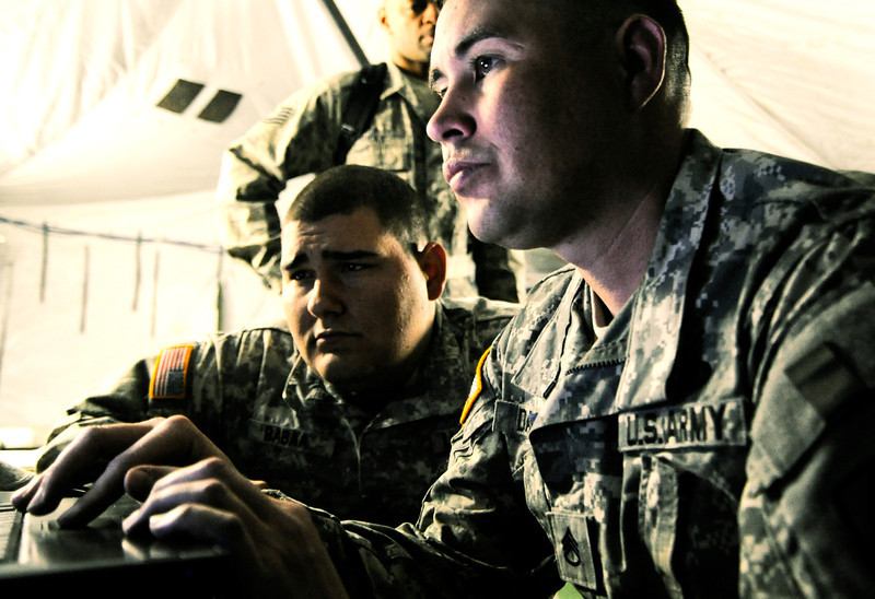 U.S. Army Staff Sgt. Justin Daijogo, right, with the 319th Expeditionary Signal Battalion, works on his laptop fixing a firewall issue at Fort Hunter Liggett, Calif., May 16, 2011, during exercise Global Medic 2011 and Warrior 91 11-01. Global Medic is a joint training exercise for theater aeromedical evacuation system and ground medical components designed to replicate all aspects of combat medical service support. (U.S. Air Force photo by Tech. Sgt. Chris Hibben/Released)