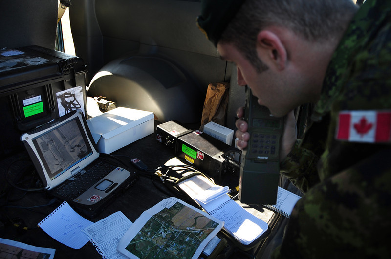 Canadian army Lt. Alex Prymack, with the 1st Regiment Royal Canadian Horse Artillery, radios map coordinates to a U.S. Air Force B-1B Lancer aircraft while examining live footage from a Sniper pod during a joint training mission between U.S. Airmen and Canadian army joint terminal attack controllers in in Alzada, Mont., Oct. 28, 2010. (U.S. Air Force photo/Anthony Sanchelli/Released)