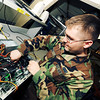 Senior Airman Trevor Winge, 22nd Communications Squadron, transfers a power supply, Dec. 28, 2009, from one computer to another with a better-formatted motherboard, a computer's main circuit board, at McConnell Air Force Base, Kan. Airman Winge works in the personal computer maintenance section of the 22nd CS Communications Focal Point. Airmen in h is section are responsible for fixing and upgrading work-related computers for Team McConnell members. (U.S. Air Force photo/Senior Airman Maria Ruiz)