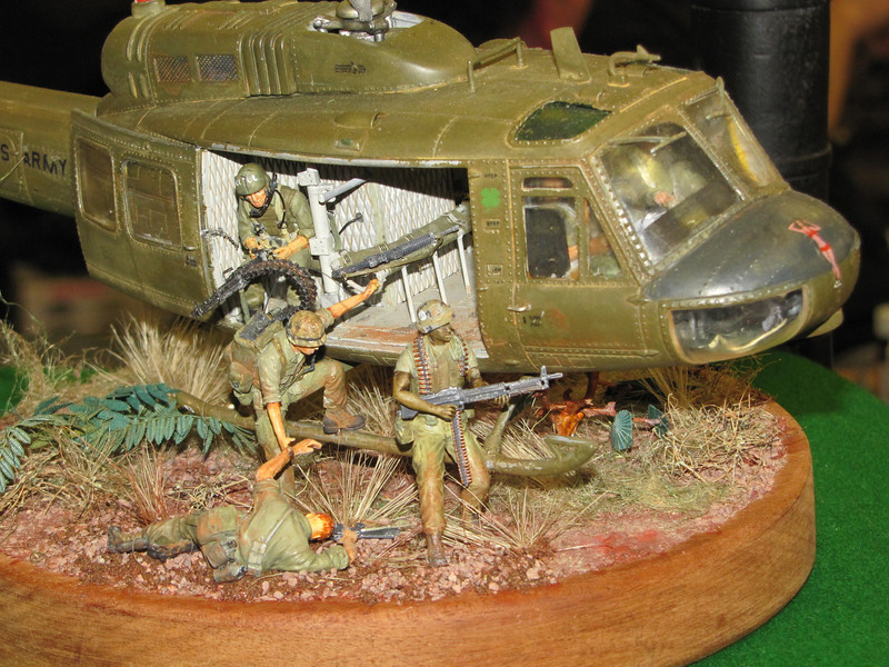 A plastic model kit diorama of a Vietnam War-era UH-1B 'Huey' helicopter off-loading troops at a landing zone