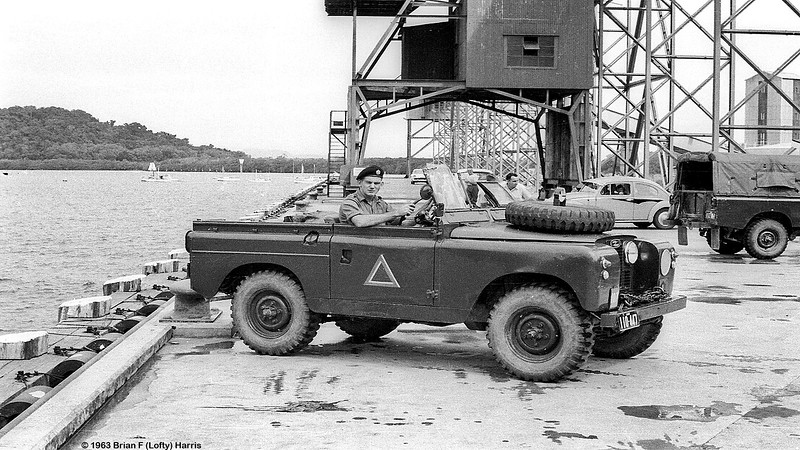 Trooper Eric (Speed) Burton drives a Landrover SWB sporty 106mm gun carrier on Mourilyan wharf